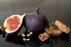 Figs, dried figs, half of fig, walnut and pine nuts on black bac Royalty Free Stock Photos