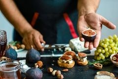 Free Figs Fruit In Hands In The Kitchen. Bruschettas With Figs, Blue Cheese And Walnuts On Grilled Crusty Bread. Food Recipe Concept Stock Photography - 135367852