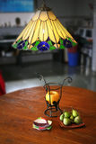 Figs, fruits and designer  lamps. Appetising fruit spread on teak wood table and  handcrafted lighted lamp made from real semi precious  gem stones in Indian Royalty Free Stock Photography