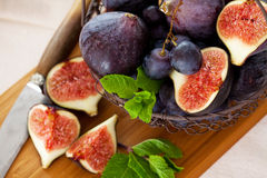 Figs and grapes. Fresh figs and grapes with green mint leaves Stock Image