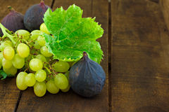 Figs and grapes on wooden table Stock Photos