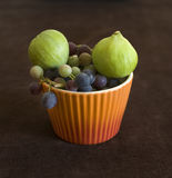 Figs and grapfruits. Green figs and grapes in an orange bowl Stock Photo
