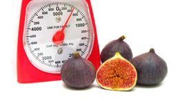 Figs and kitchen scales close up on a white background Stock Photography