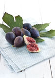 Figs with leaves. Fresh black mission figs with leaves on rustic blue napkin royalty free stock photography