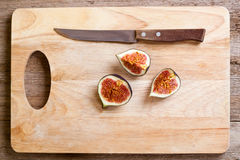 Figs and old knife on wooden board Stock Photography