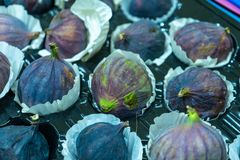 Figs in a paper containers are put up for sale on fruit market stock image