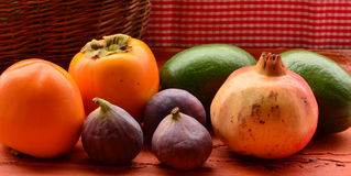 Figs, persimmons, pomegranate and avocados on rough background Stock Photo