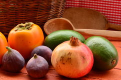 Figs, persimmons, pomegranate and avocados on rough background Royalty Free Stock Image