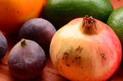 Figs, persimmons, pomegranate and avocados on rough background Royalty Free Stock Photography