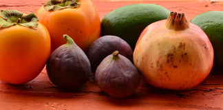 Figs, persimmons, pomegranate and avocados on rough background Stock Photography