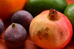 Figs, persimmons, pomegranate and avocados on rough background. Vintage theme Stock Photo