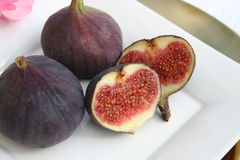 Figs. Plate with figs, whole and divided, showing fruit meats Royalty Free Stock Photo