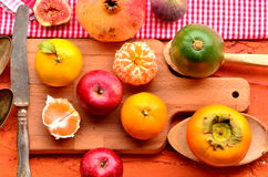 Figs, pomegranate, avocado, apples and mandarins (tangerines) on rough background. Still life theme. Stock Images