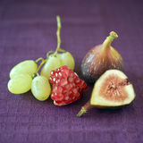 Figs pomgranate and grapes. Still life image of a part of pomegranate, grapes, a whole fig and a slice of fig on purple cloth Royalty Free Stock Images