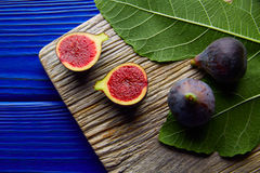 Figs raw cutted fruits and fig tree leaves on blue Stock Images