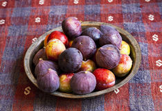 Figs and red plum. Bowl of fresh figs and red plum on the rug royalty free stock photo