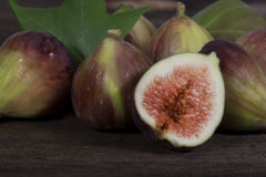 Figs. Several black figs on wood surface, front fig open exposing ripe center stock photography