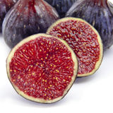 Figs. Some figs, one of them cut in half, on a white background Stock Image
