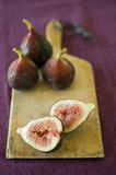 Figs still life 2. Still life three whole figs and one sliced on a wooden cutting board Stock Photo