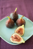 Figs still life. Still life three whole figs and one sliced on blue plate Royalty Free Stock Image
