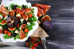 Figs, thinly sliced italian ham and tender cheese salad on white plate on wooden table with ingredients on background, view from a stock images