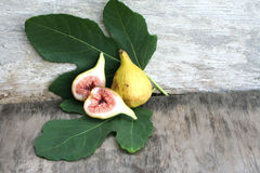 Figs on vintage background. Two figs with leaves, sliced Royalty Free Stock Photography