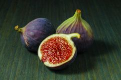 Figs, whole and half on green wooden background royalty free stock photos