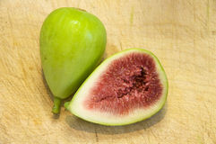 Figs on wooden chopping board. A integer fig and one open on wooden chopping board Stock Photography