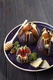 Figues cuites au four avec du fromage de chèvre, les noix et le miel du plat en céramique et du fond en bois brun, dessert turc t photographie stock libre de droits