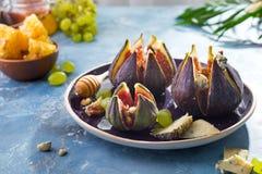 Figues cuites au four avec du fromage de chèvre, les noix et le miel du plat en céramique et du fond concret bleu, dessert turc t photo stock