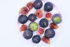 Figues entières et coupées en tranches d'un plat rose sur le fond blanc photos stock