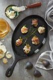 Figues et fromage enveloppés en viande sur une casserole de fonte Image libre de droits