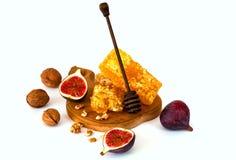 Figues fraîches avec les écrous et le miel sur un conseil en bois sur un fond blanc image stock