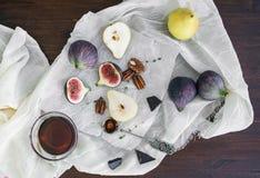 Figues fraîches, chocolat, poires et écrous pekan avec du miel sur un bois Image stock