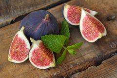 Figues fraîches délicieuses avec la menthe sur la table Photos stock