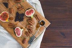 Figues fraîches et écrous pekan avec du miel sur un conseil en bois Images libres de droits