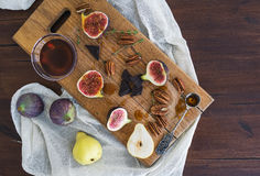 Figues fraîches, poires et écrous pekan avec du miel sur un conseil en bois Photo libre de droits