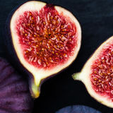 Figues fraîches sur le fond noir Belles figues violettes bleues avec Photographie stock libre de droits