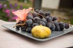 Figues jaune pâle et un groupe de raisins d'un plat gris sur un dessus de table en bois, photographie stock
