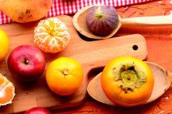 Figues, kaki, grenade, pommes et mandarines (mandarines) sur le fond approximatif Thème de vintage Photo stock