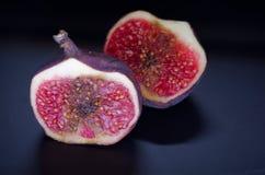 Figues mûres sur un fond noir Figues rouges sur un fond noir Images stock