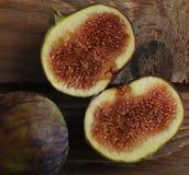 Figues mûres - deux tranches de figues sur le fond en bois dans le St rustique Photographie stock libre de droits