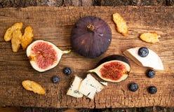 Figues, moitié des figues, brie et fromage bleu sur le vieux backgroun en bois Photos libres de droits
