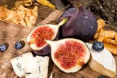 Figues, moitié des figues, brie et fromage bleu sur le vieux backgroun en bois Image stock