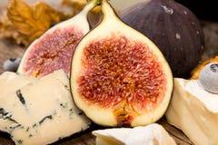 Figues, moitié des figues, brie et fromage bleu sur le vieux backgroun en bois Image libre de droits