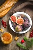 Figues, pain, miel, baies et écrous sur le fond en bois Image libre de droits