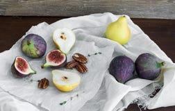 Figues, poires et écrous pekan sur un tissu blanc Photographie stock libre de droits