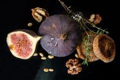 Figues, figues sèches, moitié de figue, noix et pignons sur le CCB noir Image libre de droits