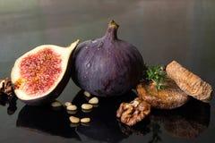 Figues, figues sèches, moitié de figue, noix et pignons sur le CCB noir Photos libres de droits