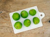 Figues vertes mûres fraîches sur une planche à découper caramic Image stock